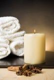 Bakgrund för den Spa massagegränsen med handduken staplade och stearinljuset med kryddor och kanelbrun anstrykning Arkivfoto