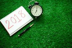 Bakgrund för det lyckliga nya året med klockan, växter och anteckningsboken har mig Royaltyfria Foton