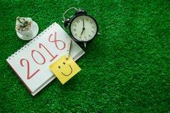 Bakgrund för det lyckliga nya året med leendeanmärkningspapper, klocka, planterar a Royaltyfri Fotografi