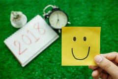 Bakgrund för det lyckliga nya året med leendeanmärkningspapper, klocka, planterar a Royaltyfria Foton