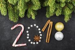 Bakgrund för det nya året av snöflingor, sötsaker, godisar, kanel, bollar numrerar året 2018 Arkivfoto