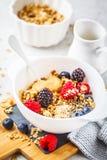 Bakgrund för frukostmat Granola med hampafrö, macapulver, jordnötsmör och bär på den vita tabellen royaltyfri foto