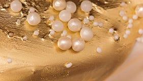 Bakgrund för guld- och pärlafondantkakaprydnad Arkivbilder
