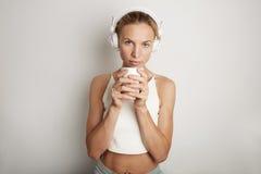 Bakgrund för hörlurar för spelare för musik för ung kvinna för stående stilig lyssnande tom vit Nätt flicka som ser rymma Coffe Fotografering för Bildbyråer