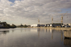 Bakgrund för kranar i port under soluppgång Royaltyfri Bild