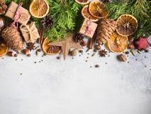 Bakgrund för ljus jul eller för det nya året med thujafilialer, julpynt, kryddor, muttrar, torkade orange skivor, sörjer kottar royaltyfri fotografi