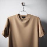 Bakgrund för mitt för Tshirt för bomull för Closeupmellanrumsbrunt hängande konkret vit tom Specificerad textur för modell högt Arkivfoto