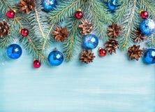 Bakgrund för nytt år eller jul: gran förgrena sig, färgrika glass bollar, kottar över den blått målade träbakgrunden, kopia fotografering för bildbyråer