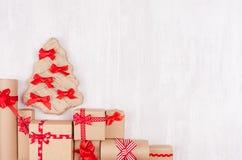 Bakgrund för nytt år - handgjort julträd och gåvaaskar av kraft papper och det röda bandet på det vita träbrädet, kopieringsutrym royaltyfri foto