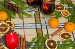 Bakgrund för nytt år med en kryddig drink, en stearinljus och apelsiner Royaltyfria Foton