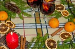Bakgrund för nytt år med en kryddig drink, en stearinljus och apelsiner Fotografering för Bildbyråer