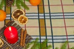 Bakgrund för nytt år med en stearinljus och apelsiner Arkivbild