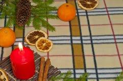 Bakgrund för nytt år med en stearinljus och apelsiner Arkivfoto