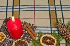Bakgrund för nytt år med en stearinljus och apelsiner Royaltyfri Foto