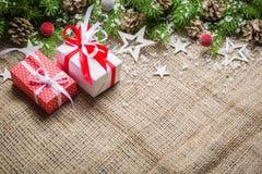 Bakgrund för nytt år och julpå en gammal bakgrund av säckväv ovanför sikt Julgranfilialer och snö, gåvor och Fotografering för Bildbyråer