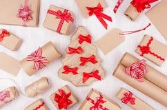 Bakgrund för nytt år - olika handgjorda askar för gåva för kraft papper med ljusa röda band och pilbågar på den vita träbakgrunde royaltyfri foto