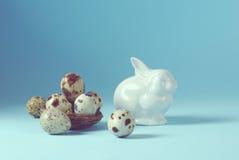 Bakgrund för påskferiestilleben med vita porslinkanin- och vaktelägg i dekorativa den tonade redetappningen royaltyfri fotografi