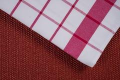 Bakgrund för produkt Kontrollerad bordduk i röd och vit bur på texturerad yttersida, sikt från över Arkivfoton