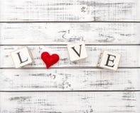 Bakgrund för röd hjärta för bokstavsFÖRÄLSKELSE lantlig trä Arkivbild
