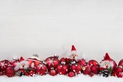 Bakgrund för röd och vit jul av trä med bollar och elaka trollet royaltyfri fotografi