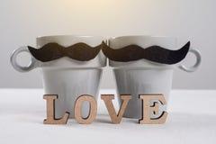 Bakgrund för romantiker för dag för valentin` s par av koppar av svarta mustascher - svarta mustascher och ett ord av träbokstäve Arkivfoton