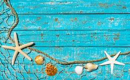 Bakgrund för sommarferie, maritimt fisknät med sjöstjärnan och snäckskal på turkosblåttträ royaltyfri foto