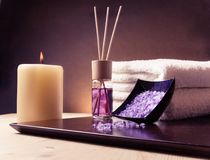 Bakgrund för Spa massagegräns med den staplade handduken, den salta doftdiffusorn och havet Arkivfoton