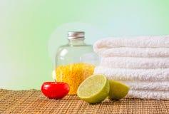 Bakgrund för Spa massagegräns med den staplade röda stearinljuset för handduk och limefrukt Royaltyfri Bild