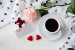 Bakgrund för St-valentindag - kopp kaffe, persikaros, tomt förälskelsekort, hjärtaformgodisar och ask för juvelgåva arkivfoto