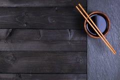 Bakgrund för sushi Soya pinnar på den svarta stenen Bästa sikt med kopieringsutrymme royaltyfri foto