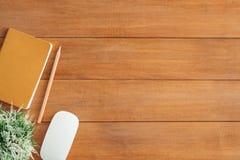 Bakgrund för tabell för kontorsskrivbord trämed åtlöje upp anteckningsböcker och blyertspenna och växt Royaltyfri Fotografi