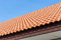 Bakgrund för tak för röda tegelplattor och för blå himmel arkivbild