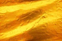 Bakgrund för textur för guld- folie för skinande gult blad mörk royaltyfria bilder