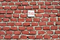 Bakgrund för vägg för röd tegelsten med nummer 56 Arkivfoto