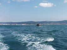 Bakgrund för våg för Black Sea yttersidasommar Sikt från yachten Exotisk seascape med moln och staden på horisont Havsnaturlugn Royaltyfria Foton