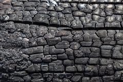 Bakgrund från en svart yttersida av det brända brände till kol träbrädet arkivbilder