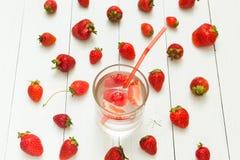 Bakgrund från jordgubbevatten och nya bär på en vit tabell Detox en sund livsstil royaltyfri fotografi