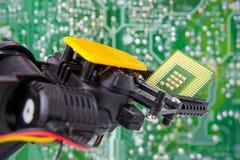Bakgrund för bräde för strömkrets för chip för robotarminnehav Fotografering för Bildbyråer