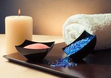 Bakgrund för Spa massagegräns med den staplade handduken, den salta stearinljuset och havet Royaltyfria Foton