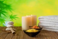 Bakgrund för Spa massagegräns med den staplade handduken, den salta stearinljuset och havet Royaltyfria Bilder