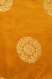 Bakgrund från ett guld- kinesiskt tyg Royaltyfri Bild