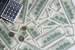 Bakgrund hundra dollar, mynt och räknemaskin Arkivbild