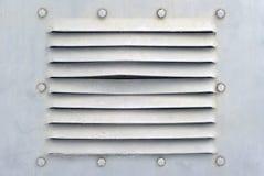 Bakgrund i den militära stilen: ett avsnitt av en grått vägg för metallight eller skal av någon pansarbil med bultar och ventilat arkivbild