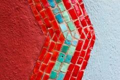 Bakgrund - ljust färgat litet avsnitt av den gamla stuckaturen och mosaiktegelplattor i rött och turkos och vit arkivfoton