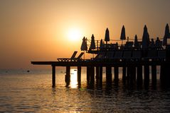 Bakgrund med den härliga solnedgångsikten av havet med varma orange och guld- toner arkivbild