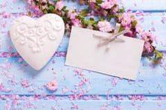 Bakgrund med eleganta sakura blommar, vit dekorativ hjärta Arkivfoto