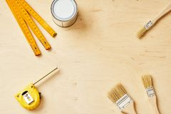 Bakgrund med en linjal, en måttband, borstar och en målarfärgcan arkivbilder