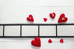 Bakgrund med en ram i form av en film och röda hjärtor S fotografering för bildbyråer