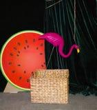Bakgrund med en rosa flamingo på ett mörker - grön bakgrund Flamingovattenmelon och päron vävde korgar flamingo Arkivbild