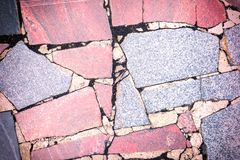 Bakgrund med en textur av en stenmosaik Stora röda och gråa fragment av granit läggas kaotiskt ut härligt Arkivfoto